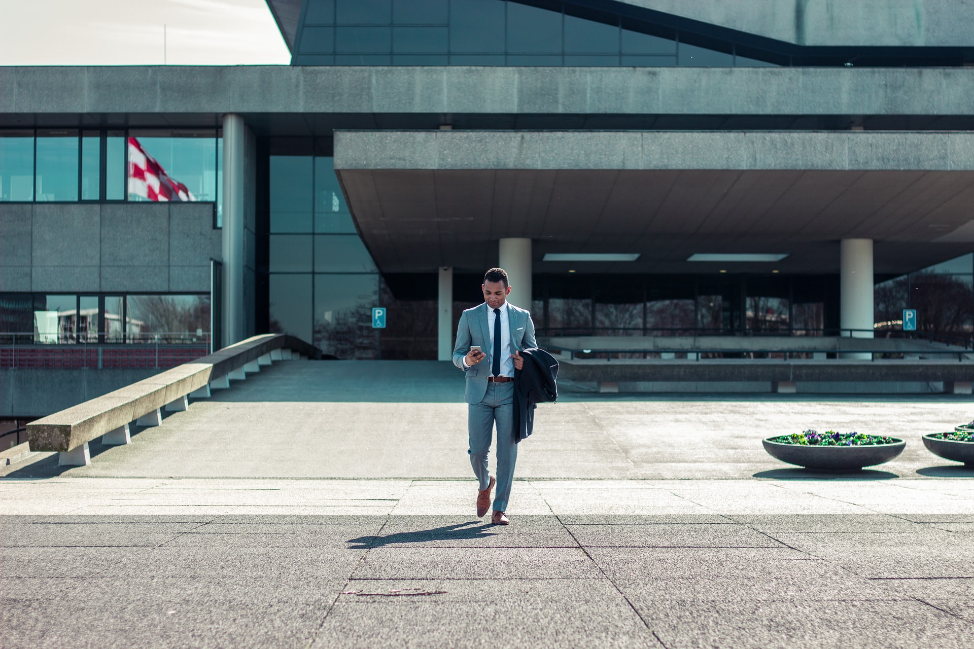 A business man walking in front of a big office building